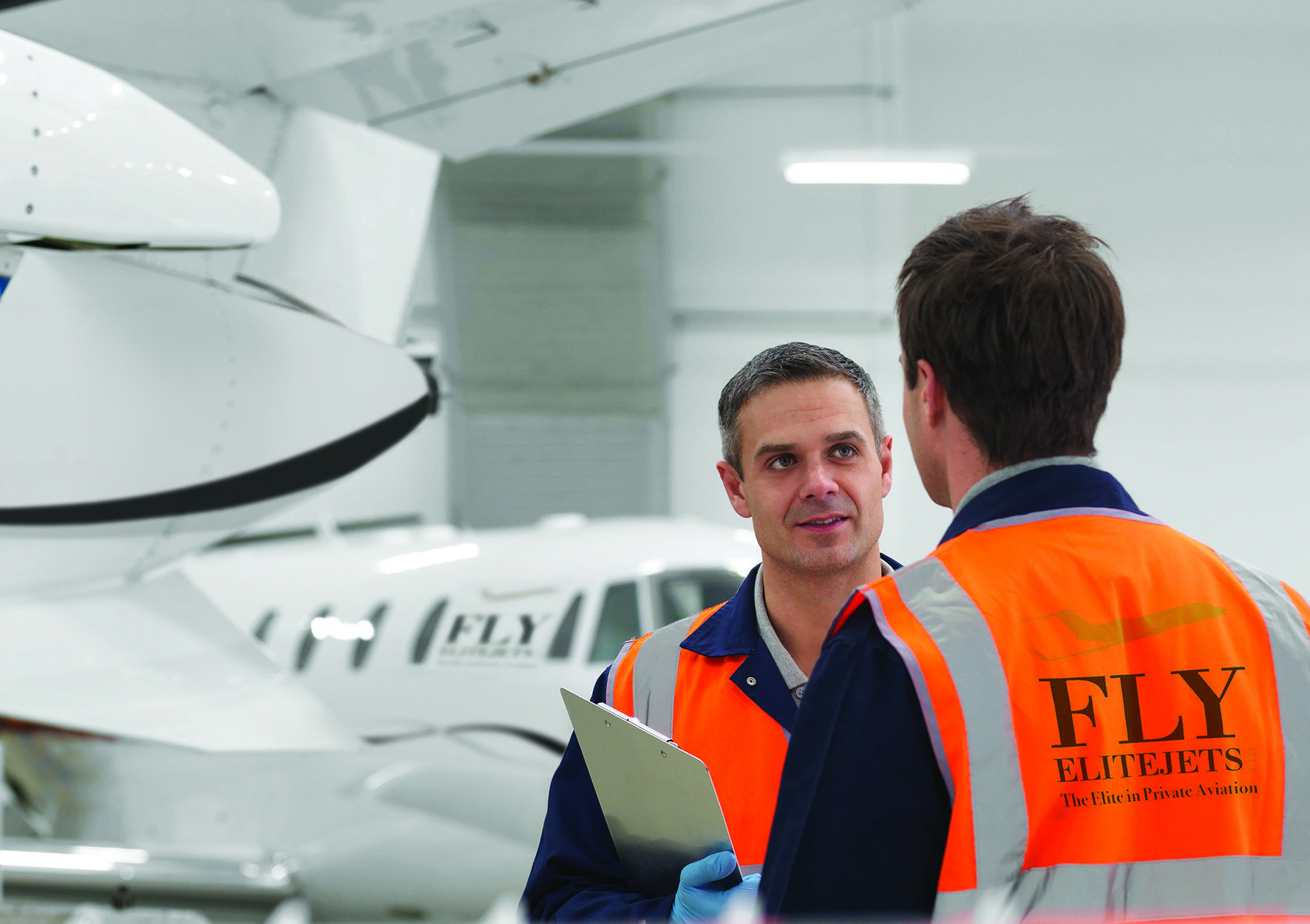 Engineers in aircraft hangar with jets